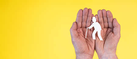 Concept of old age insurance with paper old person in hands on yellow background Foto de archivo
