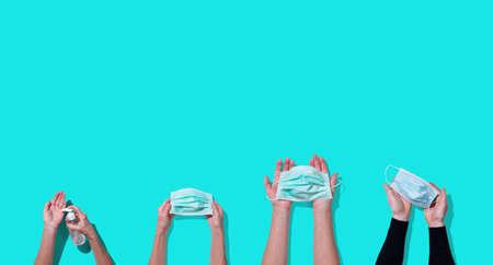 Hands holding face mask and using sanitizer bottle dispenser for preventive measure on water green color background; top view Standard-Bild - 167157385