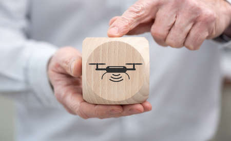 Hand holding a wooden cube with symbol of drone concept