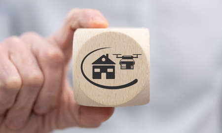 Hand holding a wooden cube with symbol of drone delivery concept