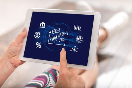 Woman using a tablet with stock market concept