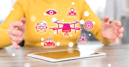 Digital tablet with drone concept between hands of a woman in background