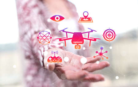 Drone concept above the hand of a woman in background