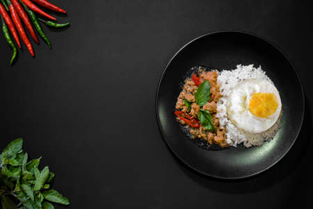Rice with pork stir fried with basil and fried egg on black background, Thai food, Street food, Image from the top view