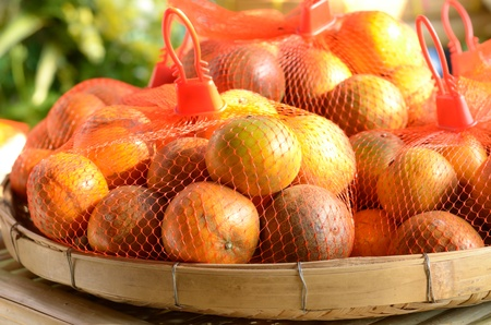 Fresh and ripe orange fruits in bamboo containers Stock Photo