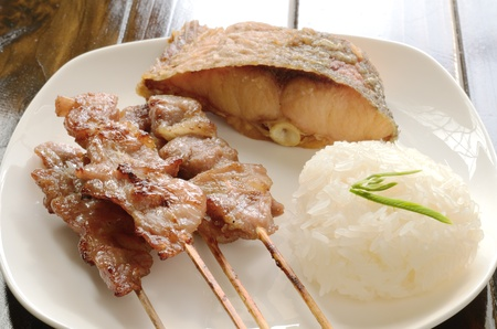 Sticky rice with grilled pork wood stick and fish fried placed on a white plate photo