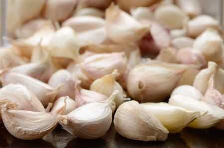 Garlic cloves are on a wooden board