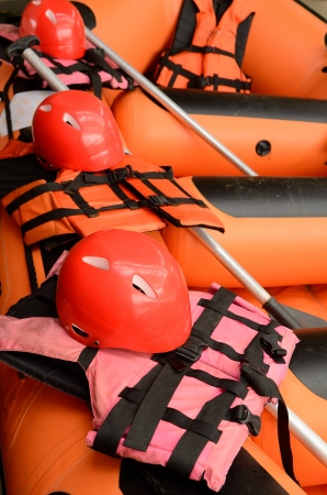 Helmet and a life jacket on a rubber raft