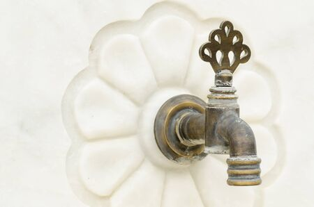 Old bronze faucet on white marble photo