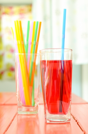 Red syrup in a glass with colorful tube on the table