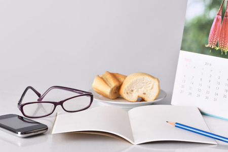 Glasses, pencil smartphone and notebook for planning