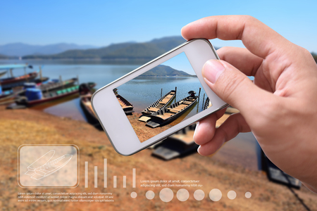 Augmented reality future technology concept. Hand holding smart phone use AR application to check safety of boat for travel. Stock Photo
