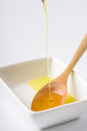 Pouring olive oil in a wooden spoon Stock Photo
