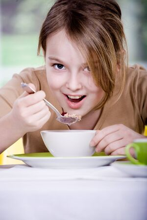 cereal bowl: young girl eating muesli from the bowl Stock Photo