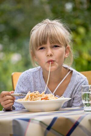 ni�os comiendo: chica comer espaguetis en el jard�n Foto de archivo