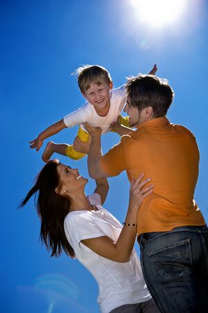 young family on the meadow at sunny day Stock Photo - 8685553