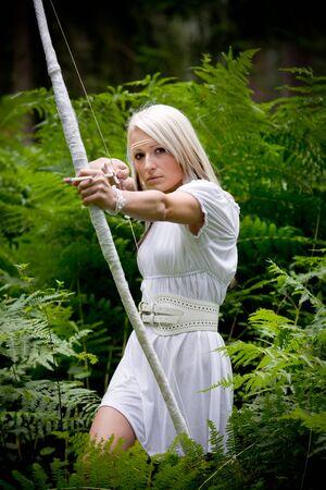 arco y flecha: una joven Amazonas con un arco en el bosque lluvioso