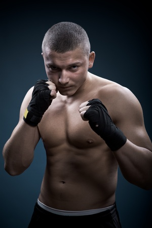 portrait of a young boxer in front of dark background