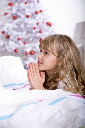 a little girl waking up in front of Christmas tree photo