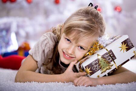 una pequeña niña vuelvete el regalo de Navidad Foto de archivo