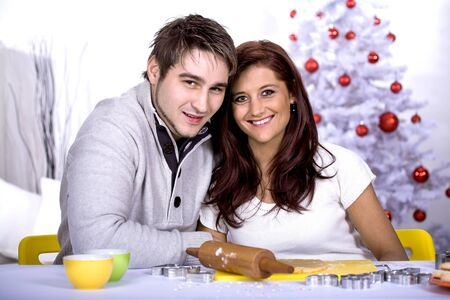 a young couple making xmas cookies at home photo
