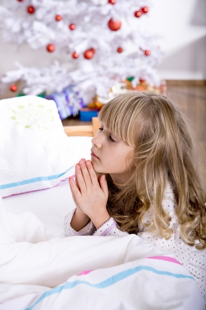 family praying: una ni�a peque�a, el despertar de �rboles de Navidad