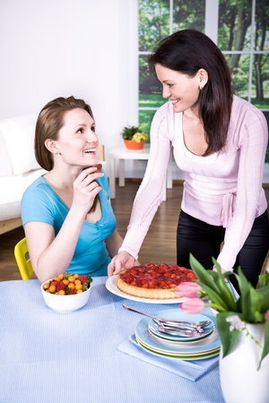 two young women with fresh strawberry cake Stock Photo - 9361471