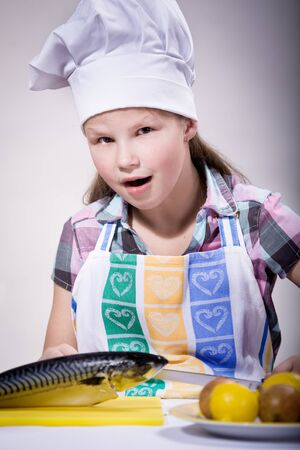 a girl cooking fish in the kitchen photo