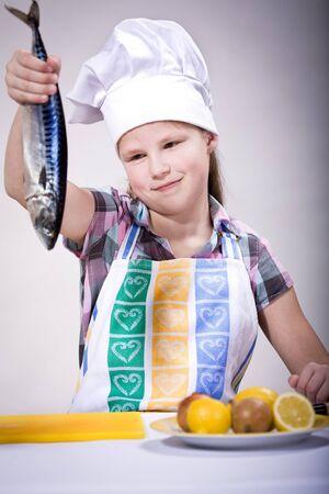 ein Mädchen Fisch in der Küche kochen