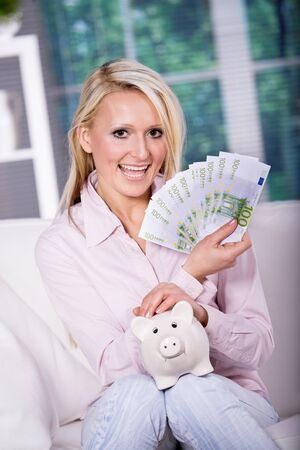 portrait of a young woman with piggybank and money photo