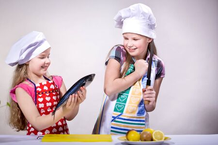 young girls cooking fish in the kitchen photo