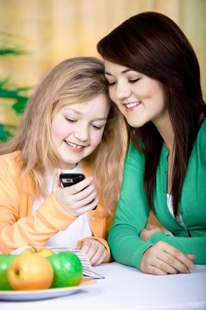 dos ni�as con un tel�fono celular en casa Foto de archivo - 9414169