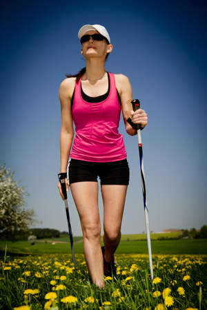 a young woman making nordic walking. outdoor shoot.