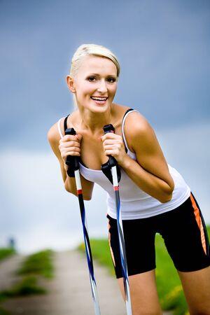 nordic walking: a young woman making nordic walking. outdoor shoot.