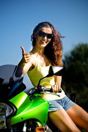 young woman riding the motorcycle photo