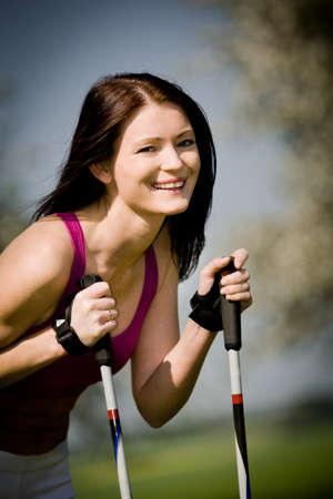natur: a young woman making nordic walking. outdoor shoot.