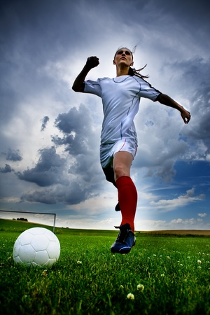 soccer kick: a young female football player on the field Stock Photo