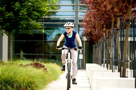A cycling woman in front of urban background Stock Photo - 9879169