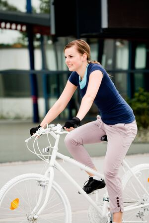 A cycling woman in front of urban background photo