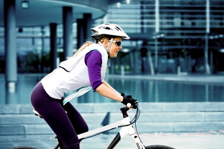 cycling   helmet: A cycling woman in front of urban background