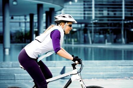 andando en bicicleta: Una mujer en bicicleta por delante de fondo urbano