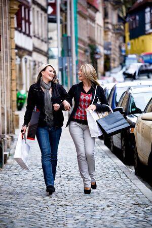 都市のショッピングの 2 つの若い女性