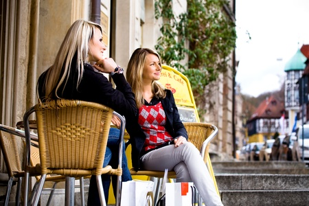 two young woman sitting at a sidewalk cafe