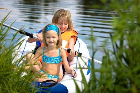 two young girls boating on the inflatable rubber dinghy on the lake photo