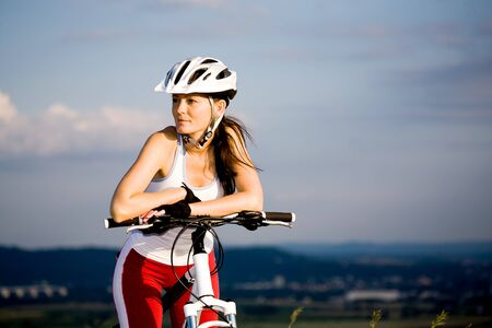 A cycling woman in front of rural landscape photo