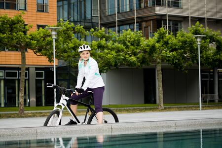 A cycling woman in front of urban background