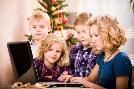 kids surfing with a laptop at the christmas tree photo