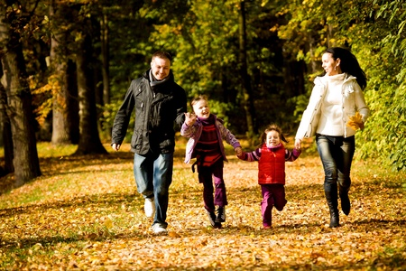 family park: portrait of a young family in the autumn park Stock Photo