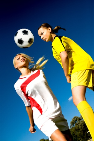 two female soccer players on the field photo