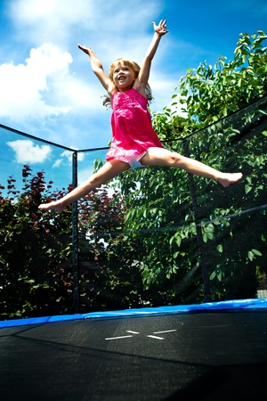 little girl jumping on the trampoline Stock Photo
